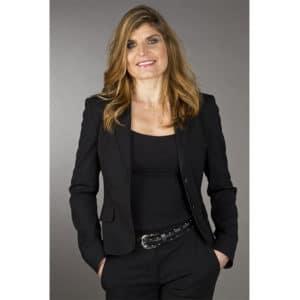 Portrait de Karine Baillet en tailleur noir mains dans les poches